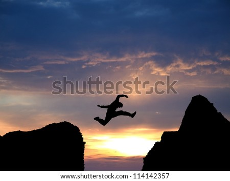 silhouette of man jumping over rocks in sunset