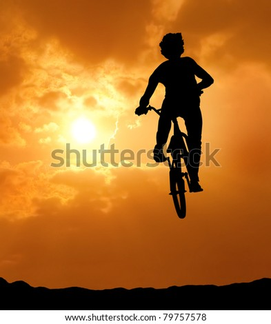 silhouette of man jumping with bicycle at sunset