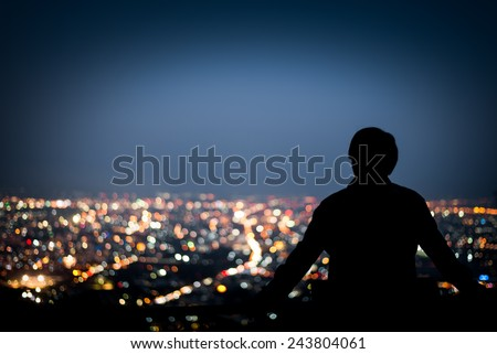 Silhouette of man looking above the city in the night #243804061
