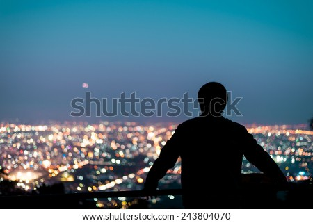 Silhouette of man looking above the city in the night