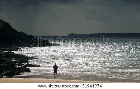 silhouette of man looking out to sea with stormy skies in the distance