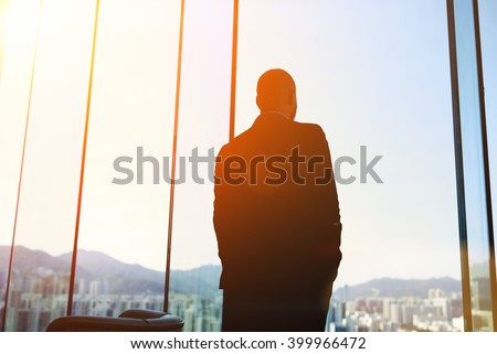 Silhouette of man managing director is examining the challenges the company after the refusal of investors in financing, while standing in evening time against office window background with copy space #399966472