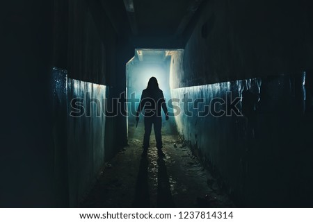 Silhouette of man maniac or killer or horror murderer with knife in hand in dark creepy and spooky corridor. Criminal robber or rapist concept in thriller atmosphere, toned