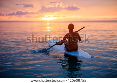Silhouette of man paddling on paddle board at sunset. Watersport near the beach on sunset