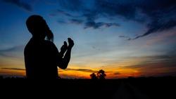 Silhouette of man praying during sunset