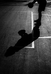 Silhouette of man preparing a free throw in a basketball game. B&W. Copy space.