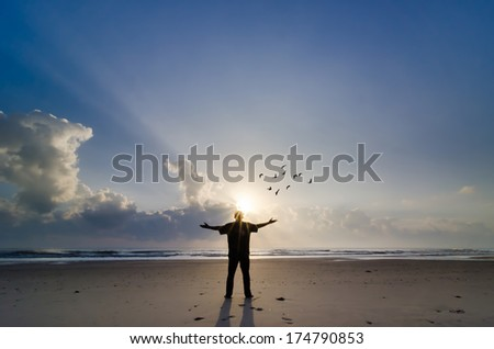 Silhouette of Man Raising His Hands or Open arms when sunrise