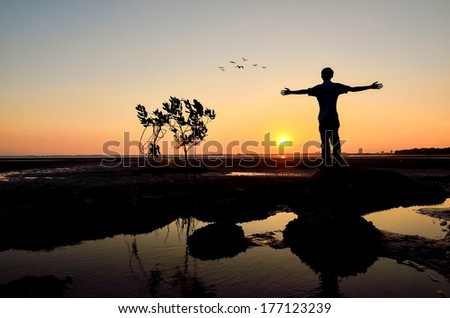 Silhouette of Man Raising His Hands or Open arms when sunset