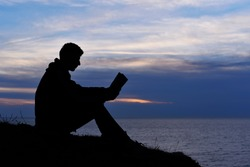 Silhouette of man reading in the sunset light, sea, ocean, nature