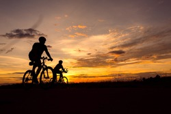 Silhouette of man ride a bicycle in sunset background.