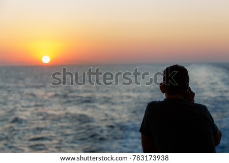 Silhouette of man standing alone on boat with blue sea and calling to someone at beautiful twilight sunset. Lonely man concept. #783173938