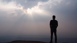 Silhouette of man standing alone on the mountain top looking at sky and sunset view Solo travel and new day inspirational concept