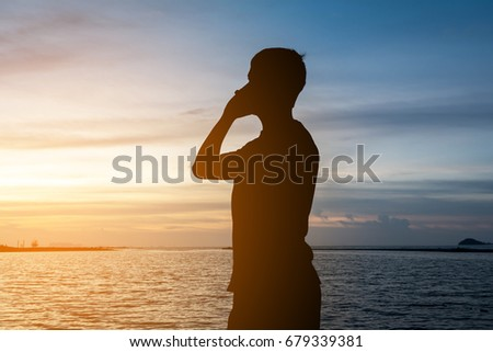 Silhouette of man standing alone on tropical beach with calm blue sea and calling to someone at beautiful twilight sunset. Lonely man concept. #679339381
