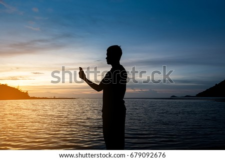 Silhouette of man standing alone on tropical beach with calm blue sea and holding smartphone at beautiful twilight sunset. Lonely man concept. #679092676
