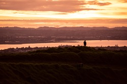 Silhouette of man standing during sunset on top of Mount Eden, Auckland, New Zealand.