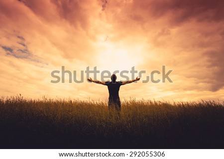 silhouette of man standing in a field at sunset #292055306