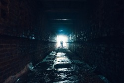 Silhouette of man standing in dark underground corridor. Light at end of tunnel concept