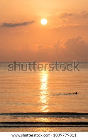 Silhouette of  man swimining in the sea with sunrise in the background on the calm Sea. #1039779811