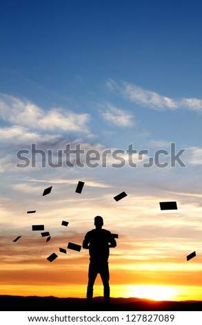silhouette of man throwing papers in sunset