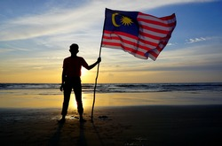 Silhouette of man waving a Malaysian flag at beach. independence day