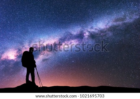 Silhouette of man with backpack and trekking poles against amazing purple Milky Way at night. Space. Landscape with man, bright milky way, sky with stars. Beautiful galaxy. Travel. Starry sky. Nature #1021695703