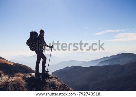 Silhouette of man with big backpack and trekking poles standing on the edge and watching to the distant mountain range in Himalayas #792740518