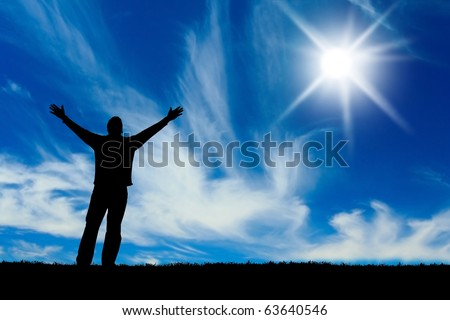 Silhouette of man with hands raised to a bright star in the sky. - stock photo