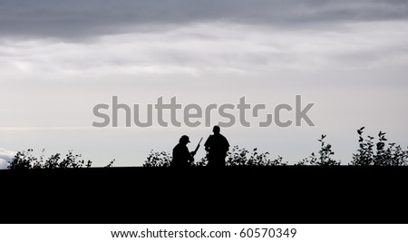 Silhouette of man with shotgun and trooper talking
