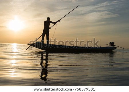 Silhouette of man with sunrise sky background, livelihoods of fishermen in Thailand