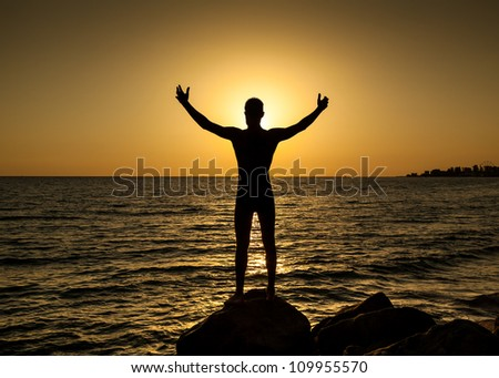 Silhouette of man with their hands in the sunset on the ocean