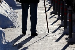 Silhouette of man with walking cane on a winter street. Concept of limping, old age, snow weather