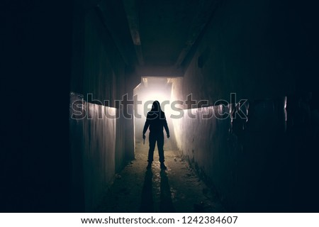Silhouette of maniac with knife in hand in long dark creepy corridor, horror psycho maniac or serial killer concept, toned Stockfoto ©