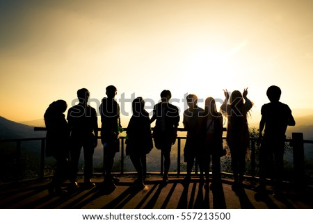 Silhouette of many friends watching sun rise with hand posts. To represent the meaning of joyful and friend relationship.