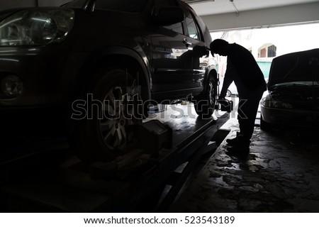 Silhouette of mechanic fixing car aligner onto car wheel in workshop garage