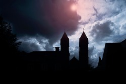 Silhouette of medieval castle and the cathedral church, night over dark sky background with the full moon