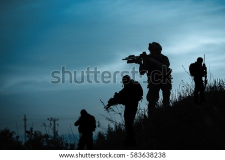 Silhouette of military soldier or officer with weapons at night. shot, holding gun, blue colorful sky, background