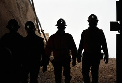 Silhouette of miners with headlamps entering a mine