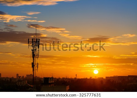 Silhouette of mobile communication antennas in an orange sunset #325777631