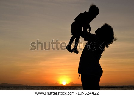 silhouette of mommy and small girl on the beach at dusk. - stock photo