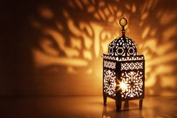 Silhouette of Moroccan ornamental lantern with burning glowing candle. Decorative shadows. Festive greeting card, invitation for Muslim holy month Ramadan Kareem. Festive night  background.