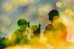 Silhouette of mother and two kids. Little children point to sky. Twinkling lights vivid blurred bokeh abstract in yellow background. Friendly family.