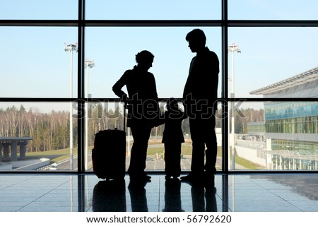 silhouette of mother, father and daughter with luggage standing near window in airport