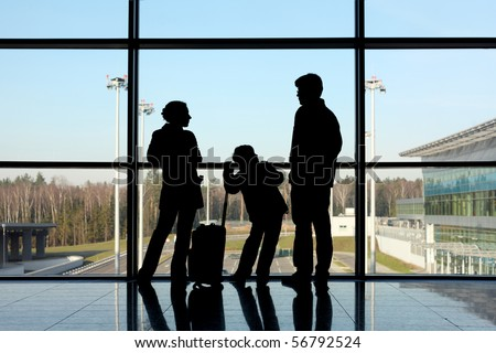 silhouette of mother, father and son with luggage standing near window in airport