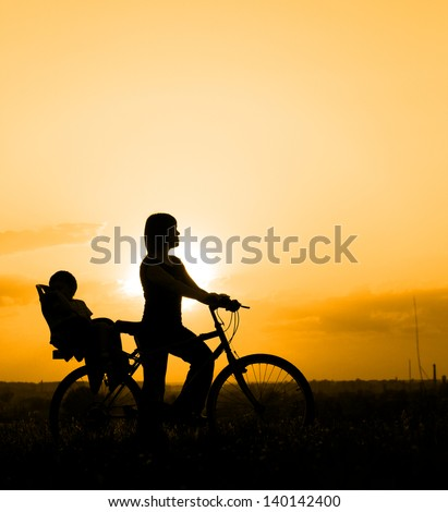Silhouette of mother riding on a bicycle with her child backlit by sunset
