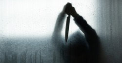 Silhouette of murderer or robber with big knife in hand behind frosted glass in  bathroom background,concept of scary crime scene of horror or thriller movies,Halloween theme