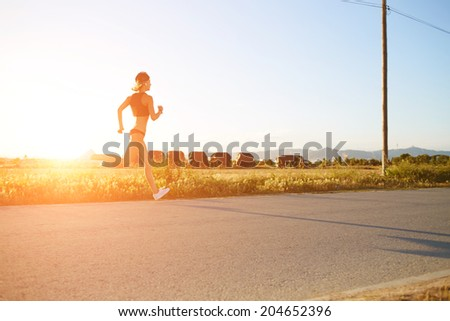 Silhouette of muscular women running on the road at bright orange t sunset, fitness and healthy lifestyle concept