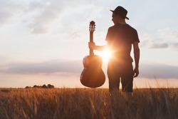 silhouette of musician with guitar at sunset field, music background