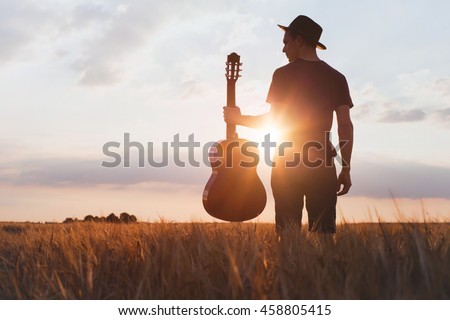 silhouette of musician with guitar at sunset field, music background #458805415