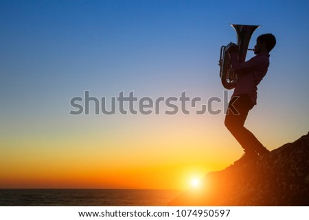 Silhouette of musician with the tuba/trumpet on rocky sea coast during amazing sunset.