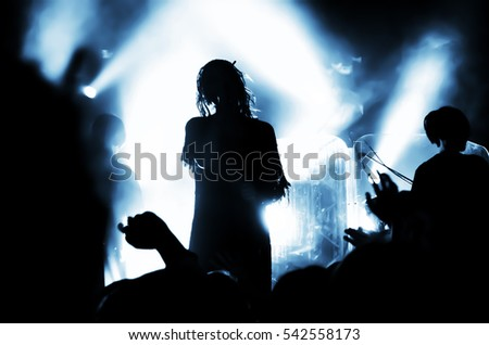 Silhouette of musicians girl with dreadlocks on the stage during a rock concert in front of a crowd of fans. People in the bright light of the lanterns #542558173